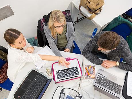 Onlinejournalismus-Studierende während einer Gruppenarbeit an ihren Laptops.